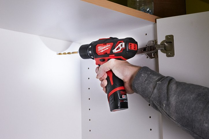 """A Milwaukee cordless 3/8"""" drill is used installing cabinets"""