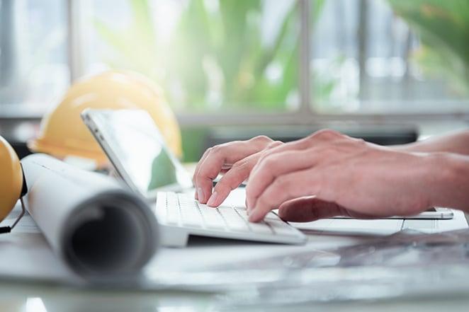 A construction BIM specialist reviews plans on computer