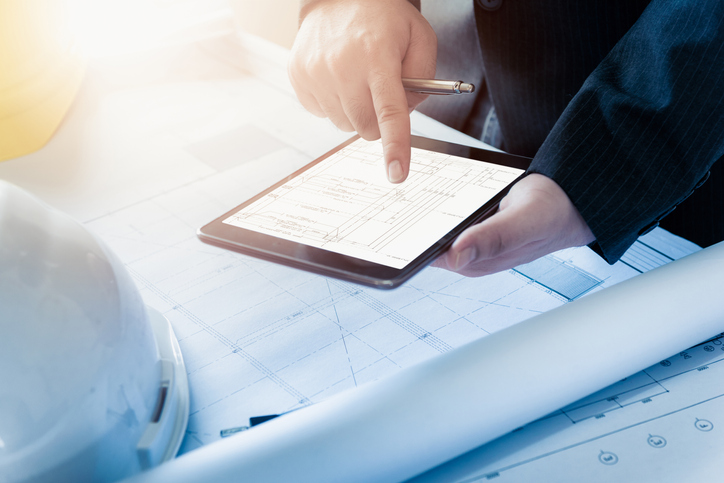 Building information modeling specialist uses BIM software on iPad beside architectural plans