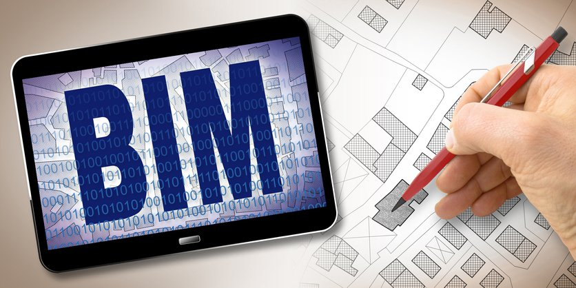 A building information modeling specialist sketches housing design beside iPad featuring BIM software