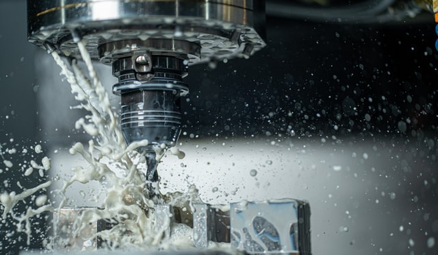 A CNC machine drills holes in steel using metal working lubricants