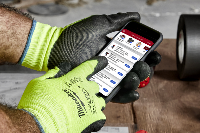 Contractor in yellow gloves operates smartphone with One-Key construction inventory app