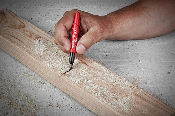 A contractor uses an INKZALL marker to draw across a two-by-four over a thick layer of sawdust