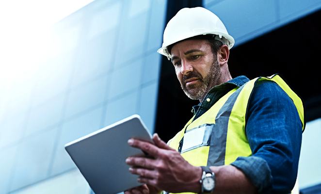 A construction manager views project details on a mobile tablet device