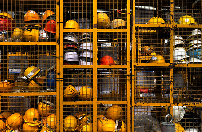 A tool crib is stocked with unused construction helmets during the day