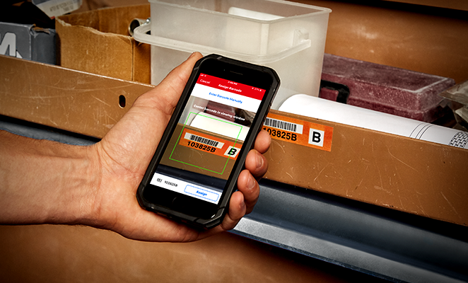 smartphone camera scans a barcode on a warehouse item