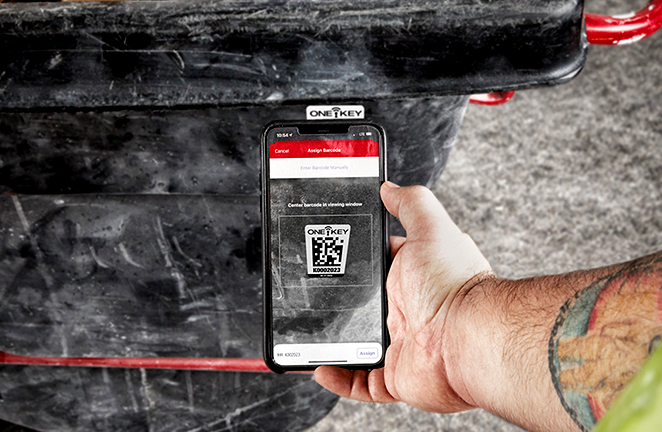 smartphone camera scans an asset ID tag on a wheeled garbage bin