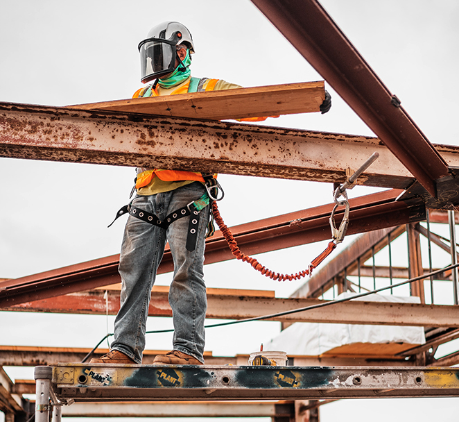 Image shows construction worker on jobsite completing work