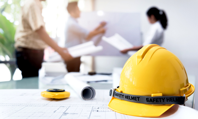 Hard hat on table next to two men and one woman in meeting outlining building plans on white board
