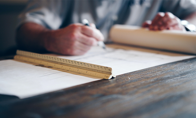 An architect drafts architectural documentation for a construction project