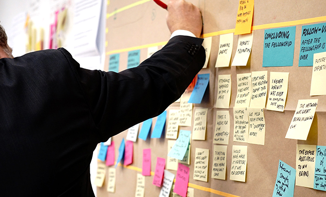 A construction project manager outlines project timelines on a cork board