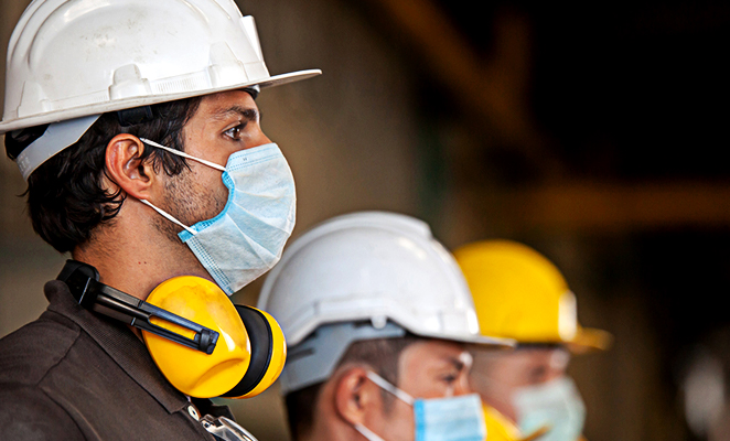 Construction workers in hard hats wear surgical face masks during COVID-19 pandemic