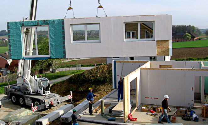 Construction workers on jobsite install prefabricated building components