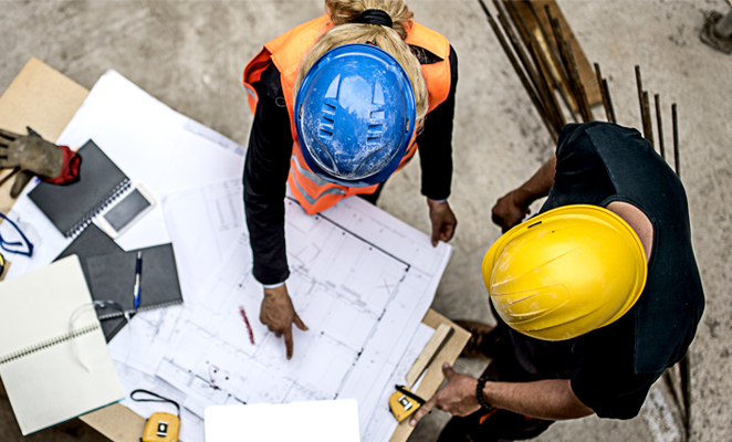 Construction workers discuss building plans together