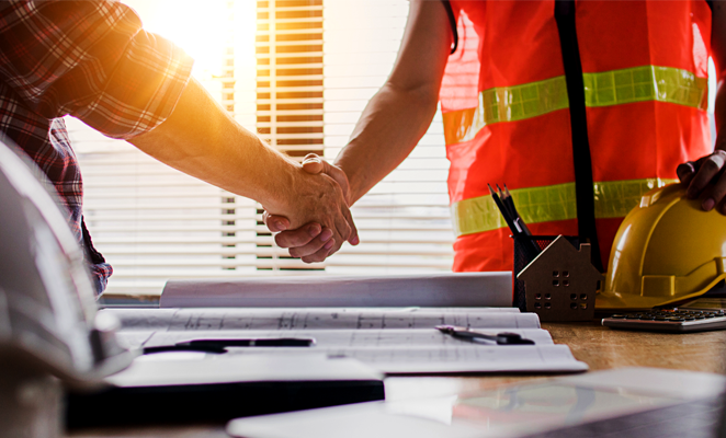 Owner-operator and subcontractor shake hands over design plans