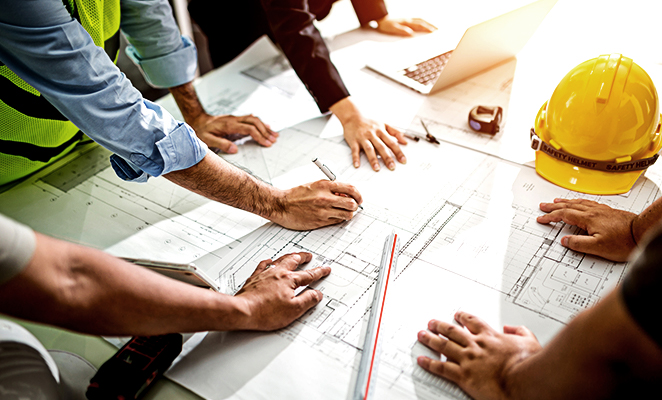 A group of contractors sketch construction plans over desk beside yellow hard hat