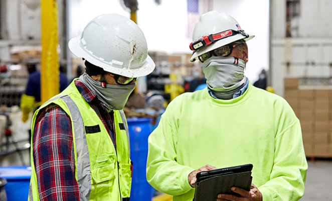 Two consulting construction workers in high visibility yellow apparel and white hard hats view iPad