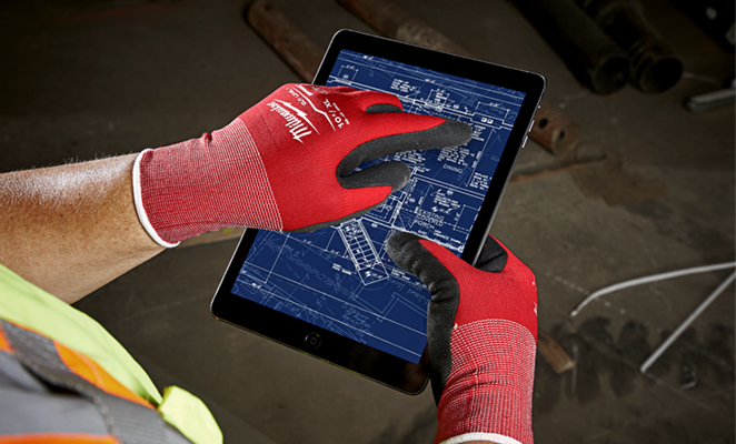 A construction worker on build site wearing red Milwaukee gloves operates BIM software on iPad