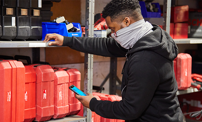 A tool room manager wearing gray Milwaukee gaiter looks at his smartphone next to shelving full of tools in red boxes