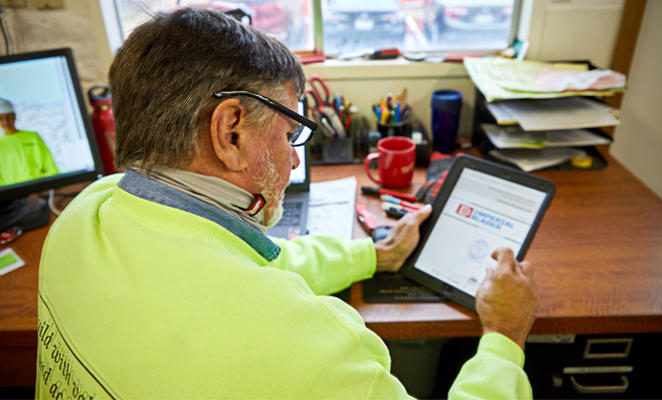 A tool room attendant views project details on iPad