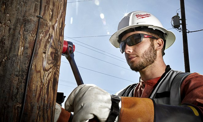 A lineman adjusting cable with ratchet wrench