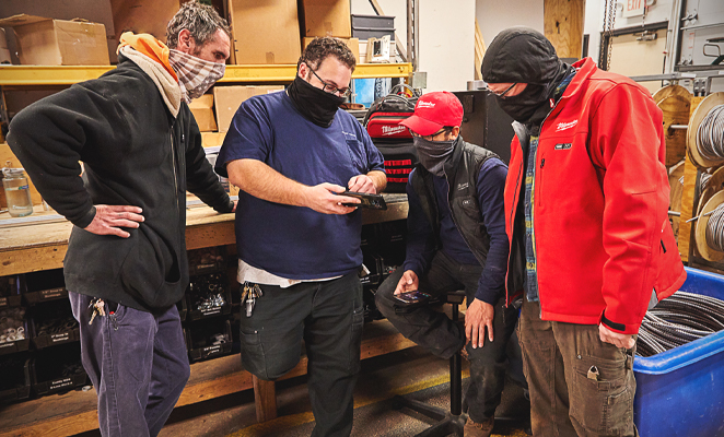 A tool team wearing face masks huddled around smartphone inspecting inventory