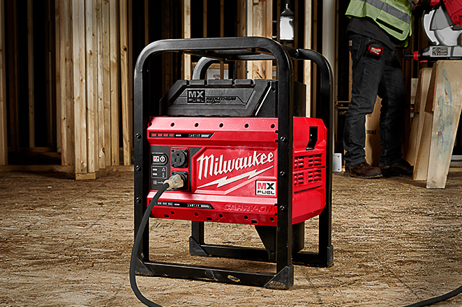 Milwaukee's MX FUEL cordless power supply in jobsite recharging tool battery while contractor operates cordless table saw