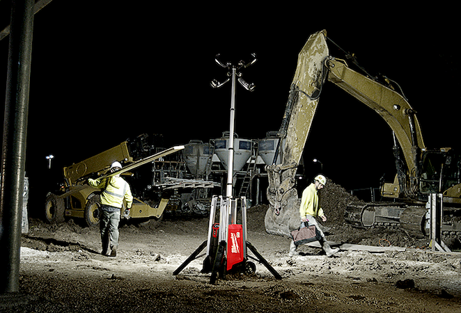 A Milwaukee light tower illuminates construction site with two workers walking opposite directions