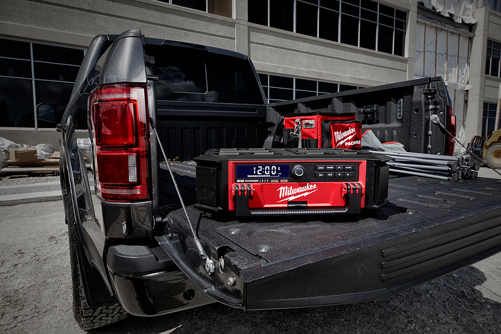 A Milwaukee PACKOUT jobsite radio sits on the open tailgate of a pickup truck beside a contractor bag and tailgate chair