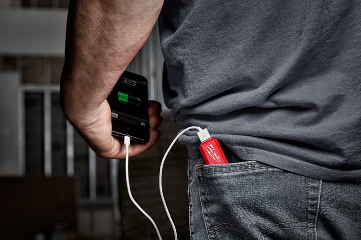 A smartphone in man's hand is charging, plugged into a Milwaukee REDLITHIUM power source in his back pocket