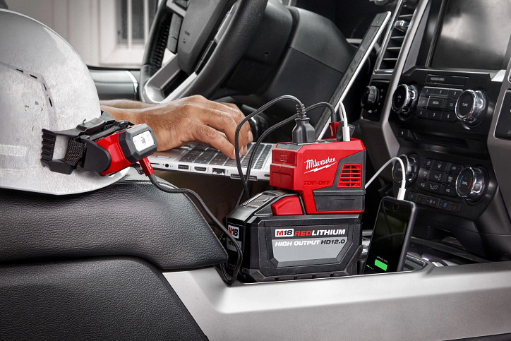 A Milwaukee M18 top-off charges a contractor's cellphone and laptop simultaneously in work truck