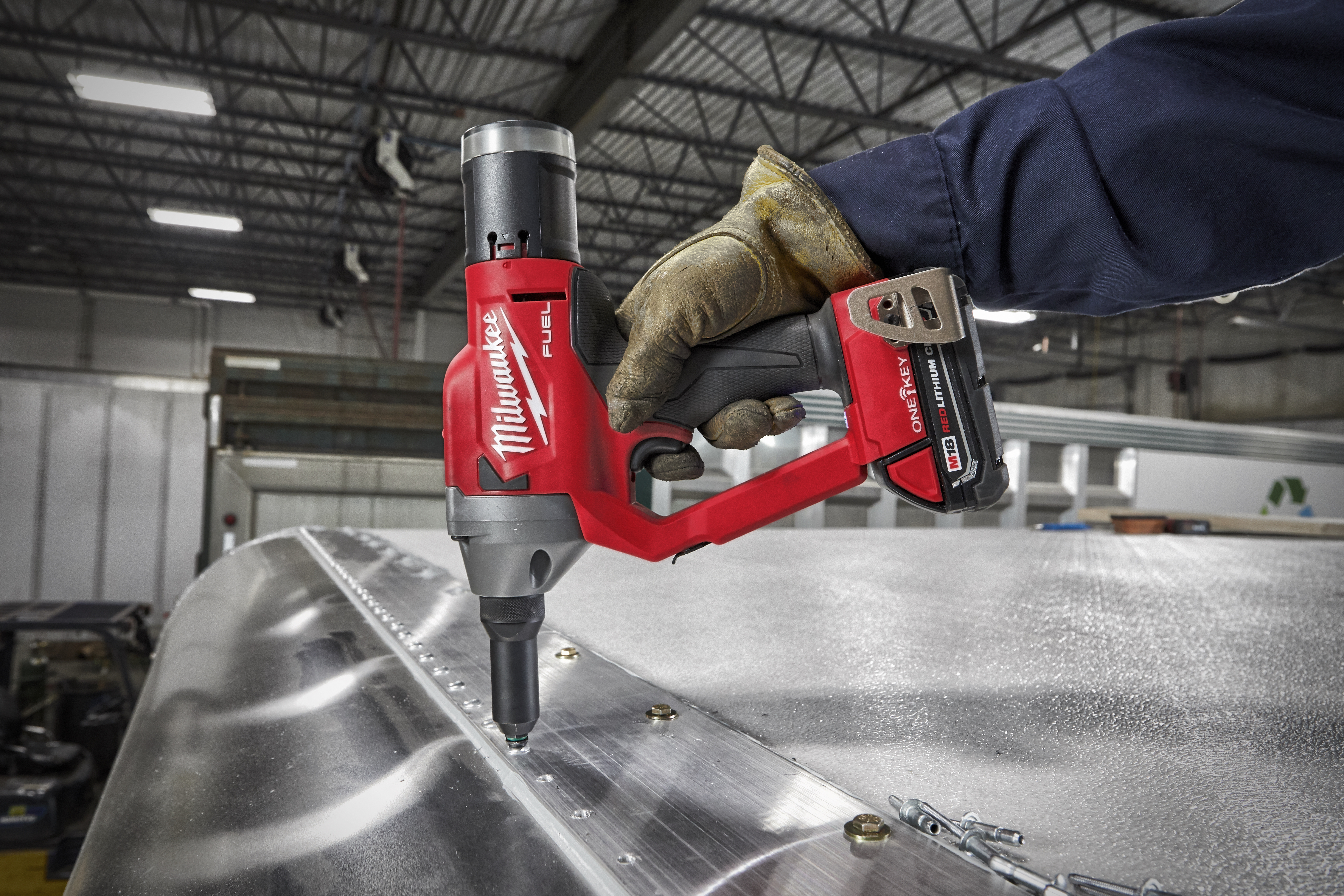 """A tradesman using a cordless Milwaukee® M18 FUEL™ ¼"""" Blind Rivet Tool to quickly secure component"""