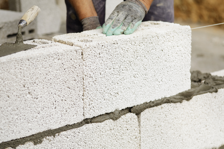 A brick mason installs cement block structured wall