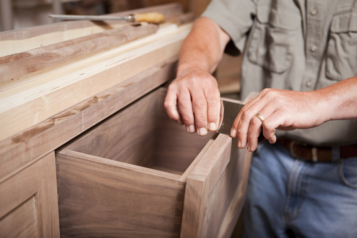 A cabinetmaker smooths wooden cabinet