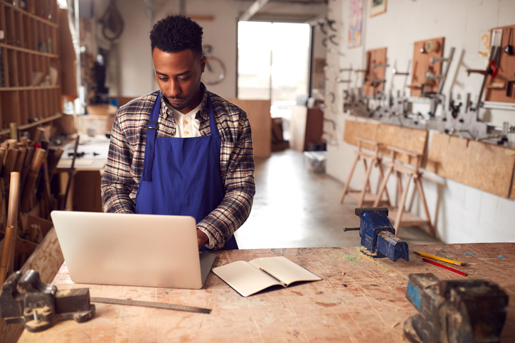 A young carpenter in woodshed uses laptop to complete customer order