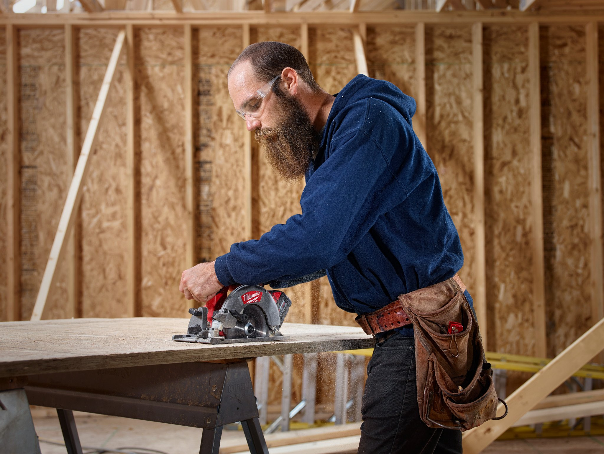 A general contractor uses a cordless Milwaukee circular saw to cut down plywood