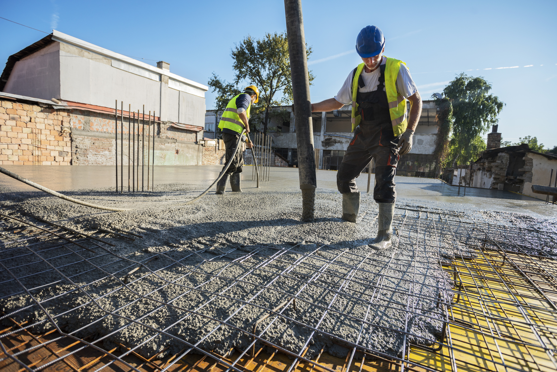 Two concrete masons lay down slab in lot beside commercial business