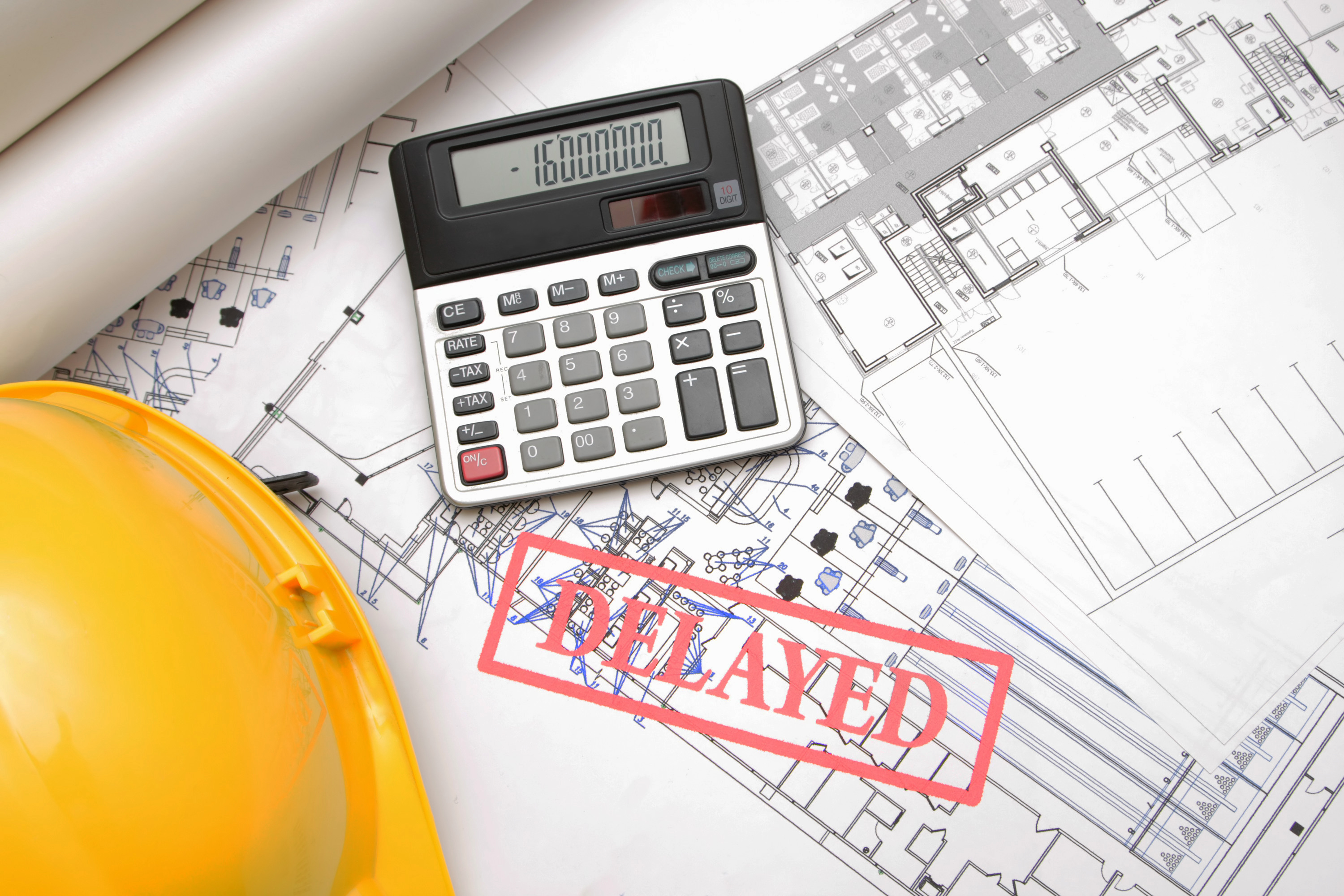 """Project plans strewn across contractor's desk beside calculator displaying negative calculations. Word """"delayed"""" overlain"""