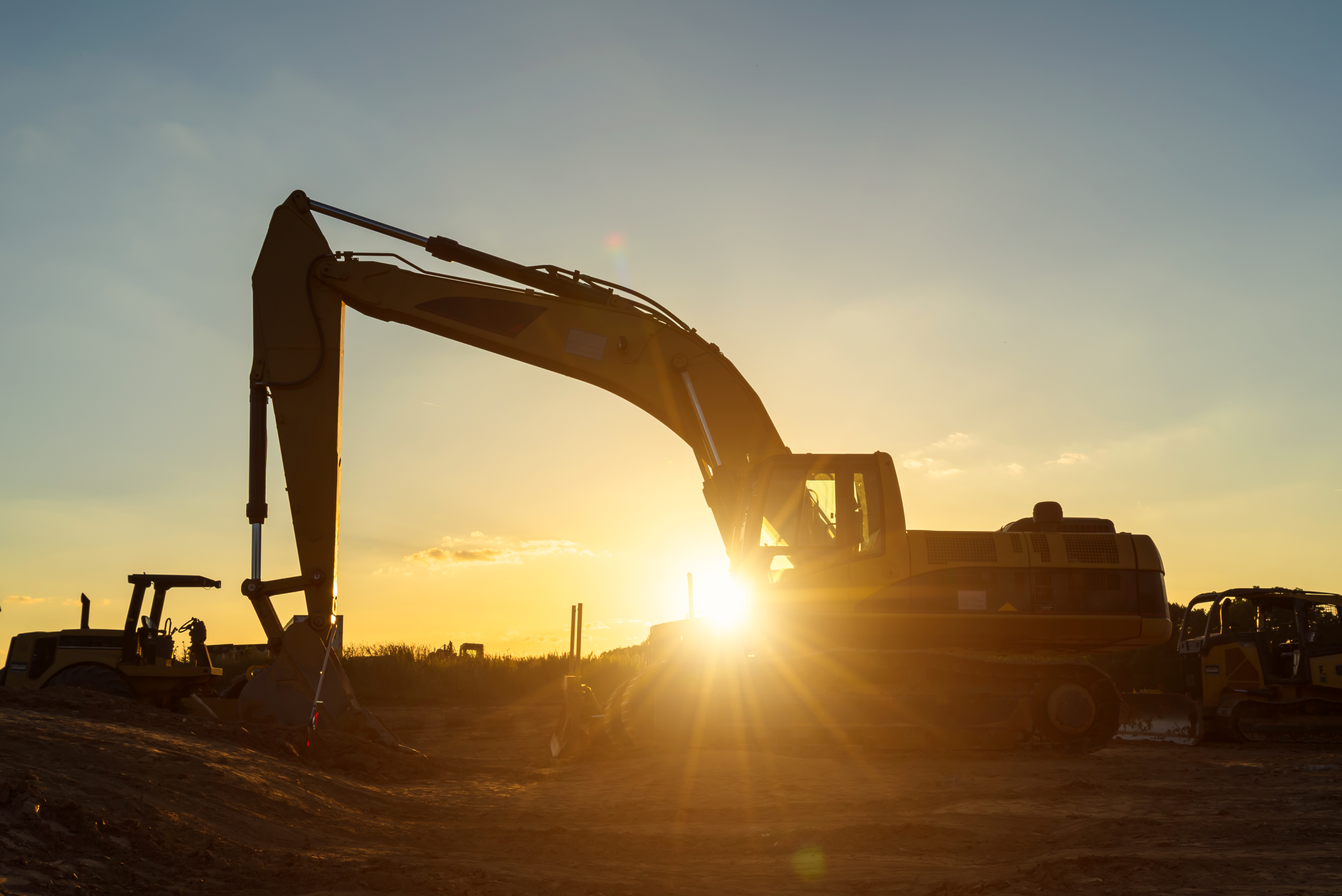A construction excavator on jobsite sits idle, unused, as sun in the sky behind it sets