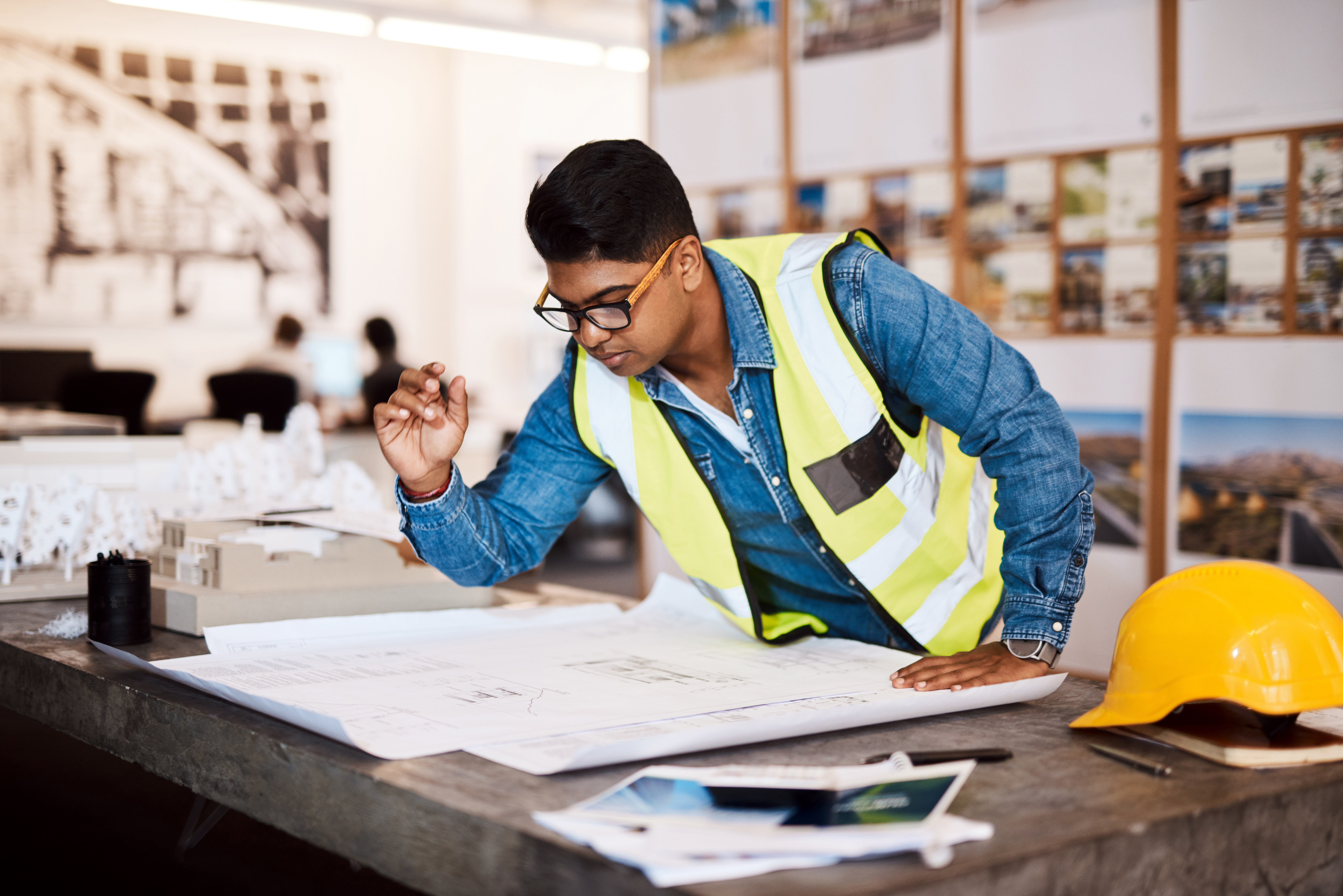 A construction project manager at desk wearing high-vis jacket, beside yellow hard hat, makes up architectural plans