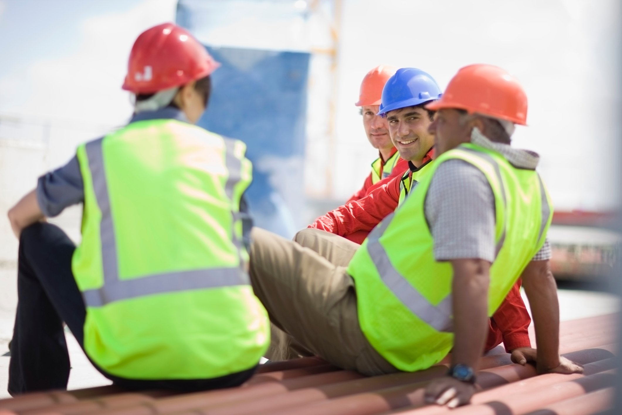 4 construction workers sitting atop roof talking among themselves