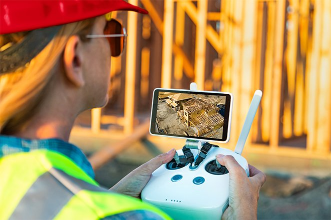 A contractor uses a remote control to operate construction drone