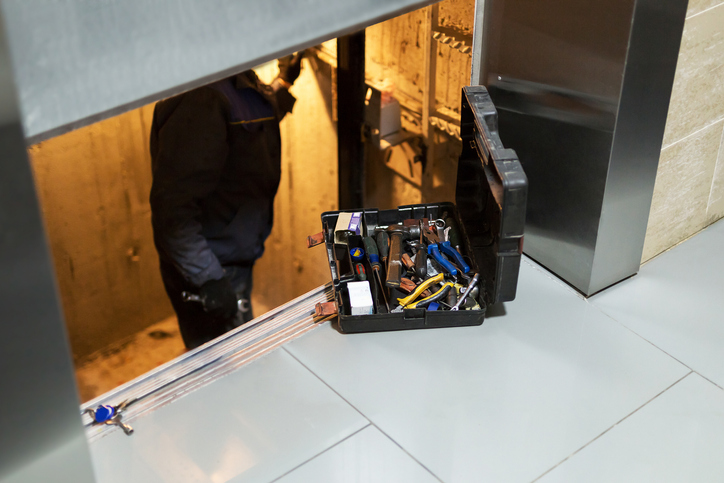 An open toolbox sits on floor beside elevator doorway, slightly ajar showing technician working