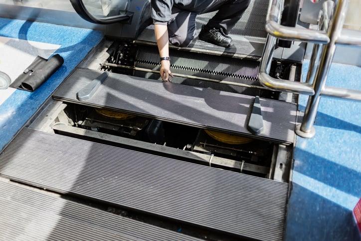 A technician services a non-operational escalator