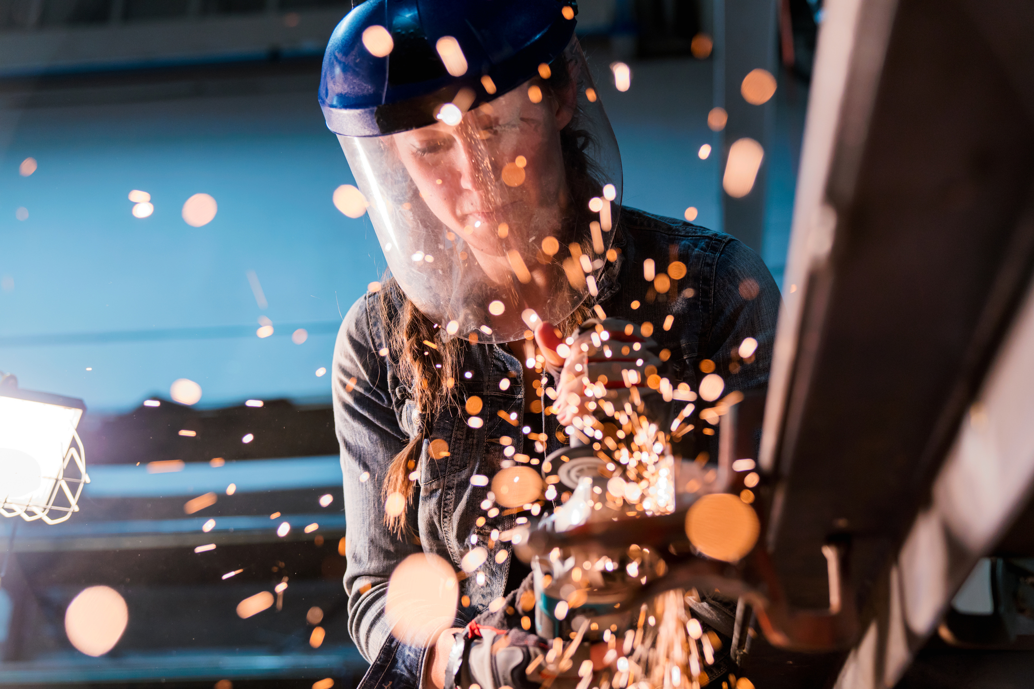 A female metalworker uses grinder tool, illuminating the foreground in flickering sparks