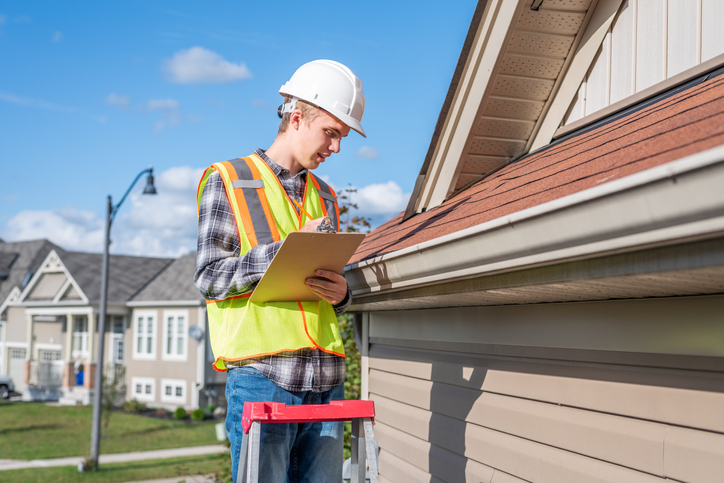 A home inspector examines shingles on roof