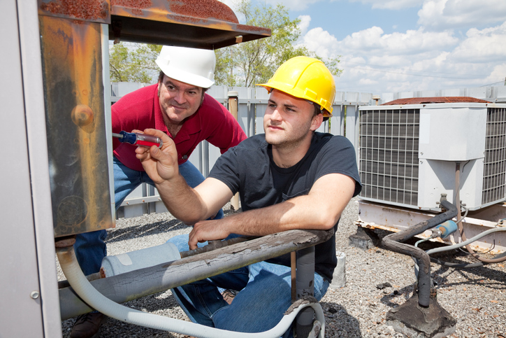 HVAC technician oversees apprentice install AC unit