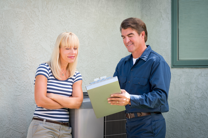 An HVAC service manager discusses AC repair with customer