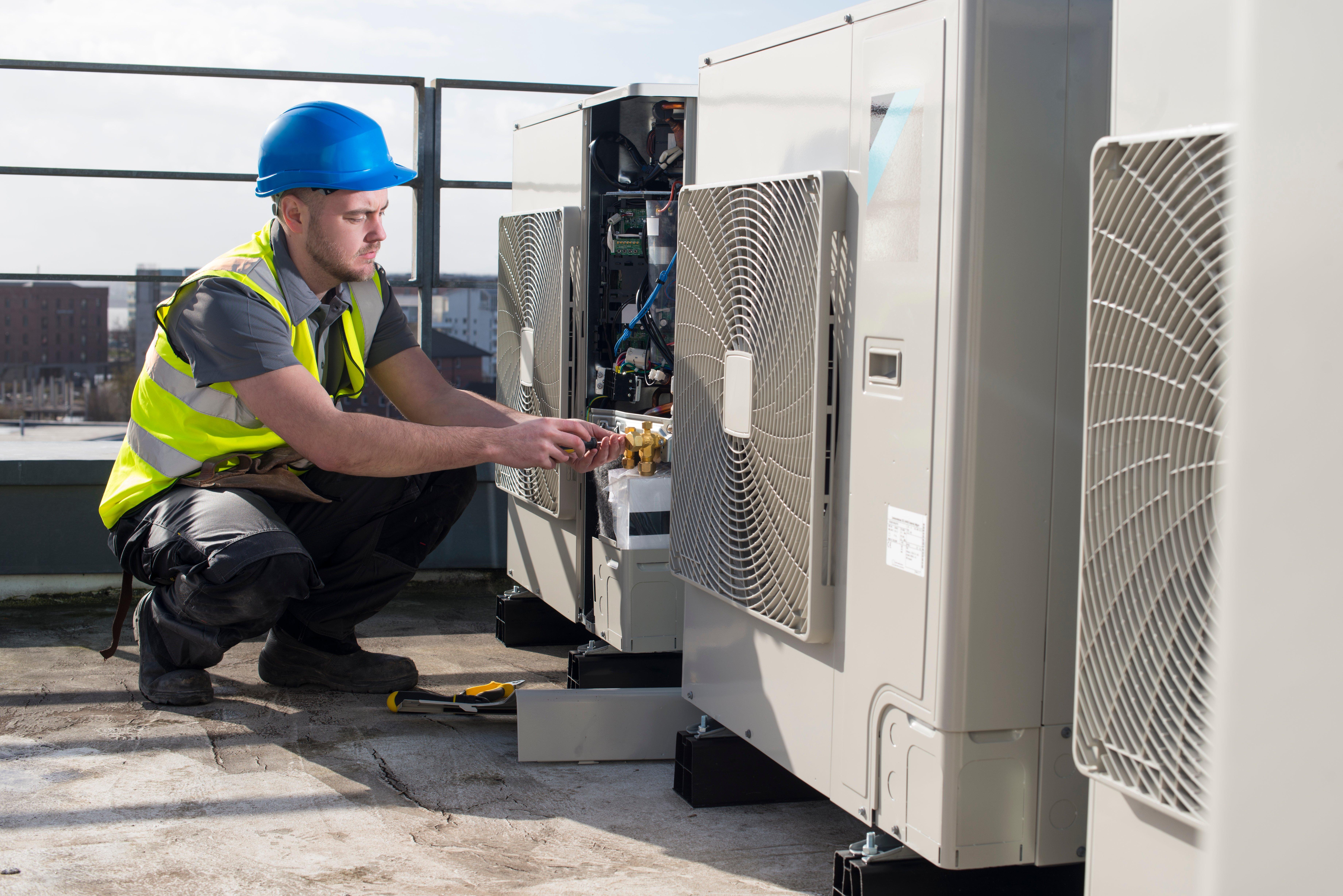 A professional commercial HVAC tech repairs AC unit