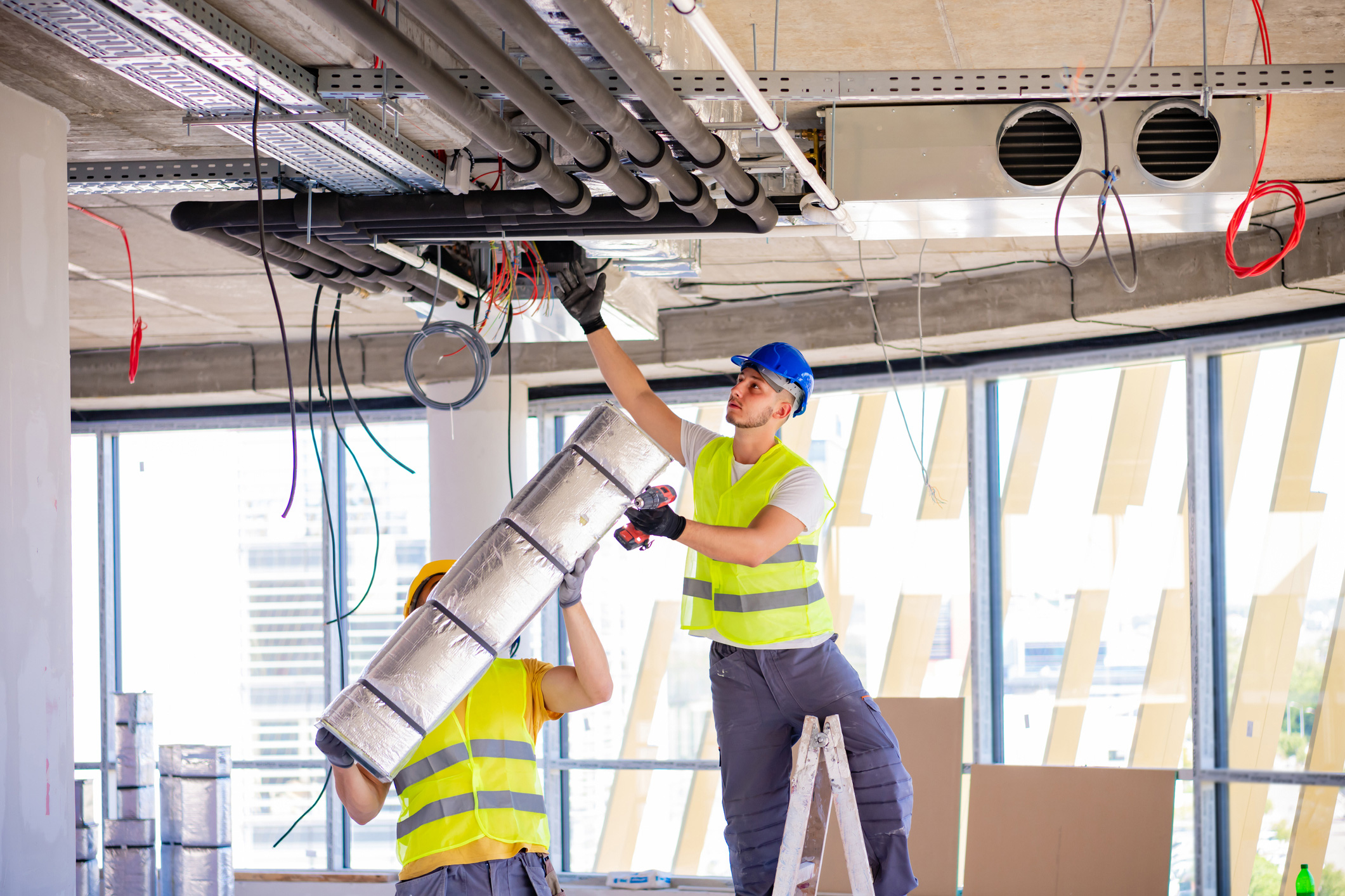 Two HVAC technicians installing overhead ductwork
